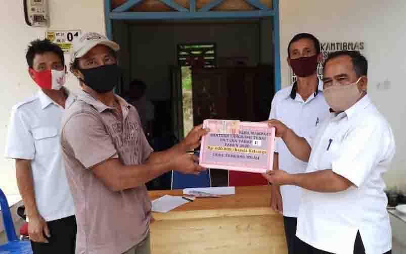 Camat Rungan Hulu, Tinjek (kanan) didampingi Kades Tumbang Mujai, Mujiadi saat menyalurkan BLT DD tahap II untuk 27 kepala keluarga,
