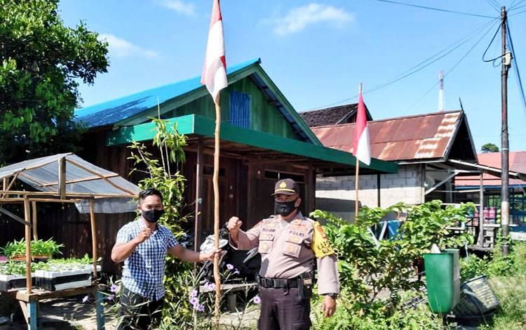 Kapolsek Bukit Batu, Iptu Muludin saat mengajak warga untuk memasang bendera merah putih di rumah masing-masing.