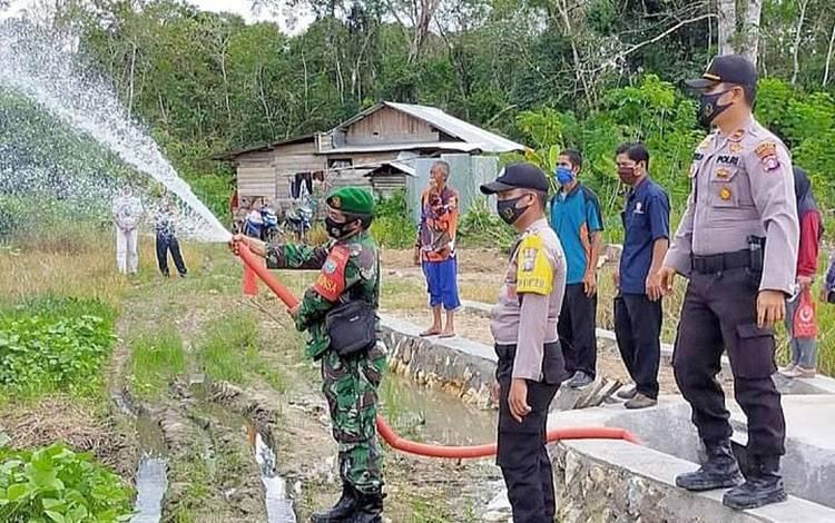 Penyiraman tanaman kacang ijo saat pencanangan desa.pantang mundur di Desa Ramania