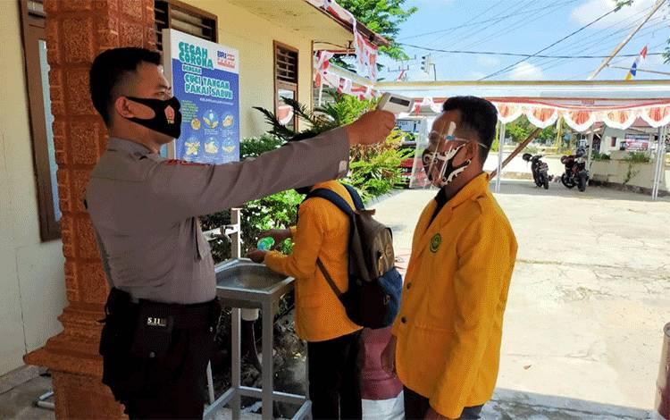 Personel Polsek saat memeriksa suhu pengunjung Polsek Kahayan Hilir.
