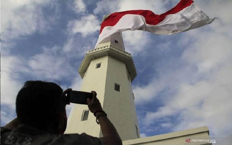 Seorang pengunjung mengabadikan berkibarnya bendera merah putih berukuran raksasa yang dipasang di puncak Menara Suar Kupang, Nusa Tenggara Timur Sabtu 8 Agustus 2020.ANTARA FOTO/Kornelis Kaha.