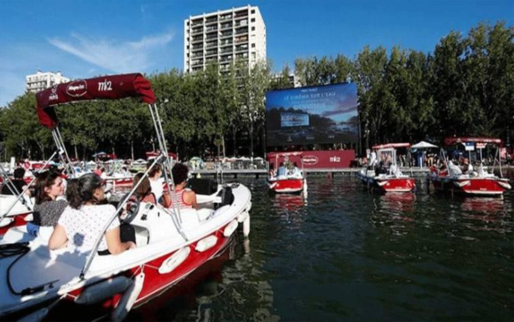 """Sejumlah penonton menyaksikan film """"Le Grand Bain"""" dari dalam kapal di Cinema on the water saat acara acara musim panas Paris Plages di sepanjang Bassin de la Villette, Prancis, 18 Juli 2020. Saat pandemi Covid-19 warga dapat menonton film dari sebuah kapal di sungai Seine. REUTERS/Gonzalo Fuentes"""