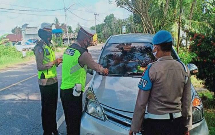 Personel Satlantas Polres Kapuas saat memasangkan stiker imbauan keselamatan berlalu lintas kepada pengendara di Jalan Trans Kalimantan.