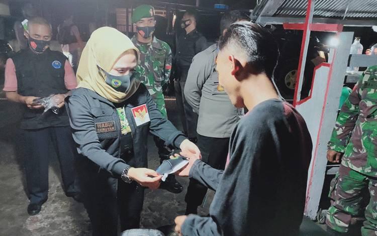 Wakil Bupati Seruyan Iswanti membagikan masker kepada salah satu warga saat kegiatan patroli bersama, Sabtu malam.