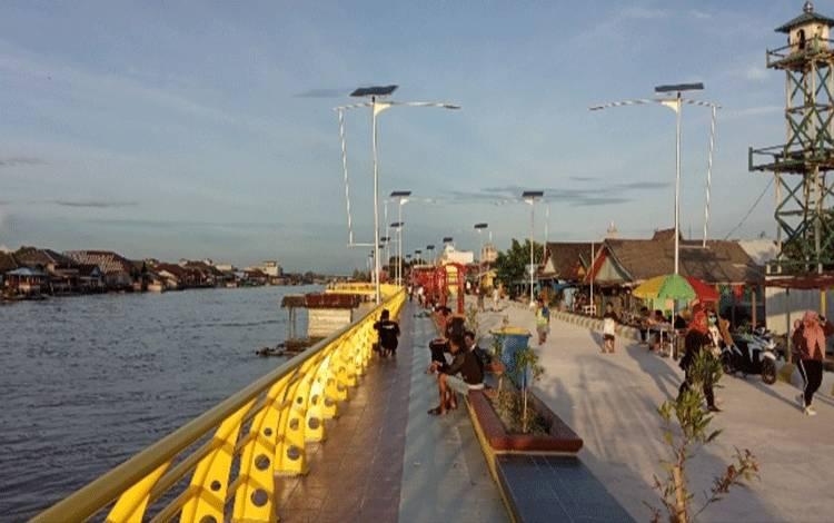 Wisatawan menikmati suasana di pinggiran Sungai Arut.