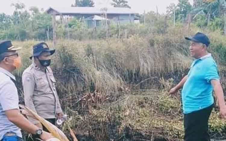 Kapolsek Pahandut Kompol Edia Sutaata dan Bhabinkamtibmas Kelurahan Menteng Toha, saat meninjau lahan milik warga yang terbakar.