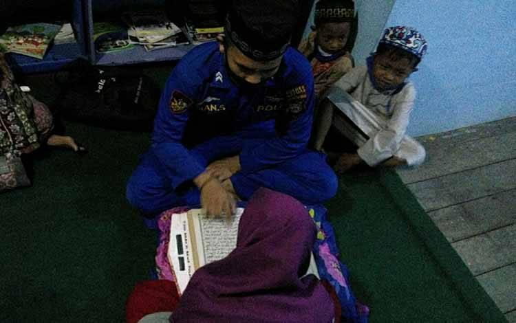 Anggota Satpolair Polres Kapuas, Briptu Iman Saputra saat mengajari anak-anak mengaji di Desa Palangkau.