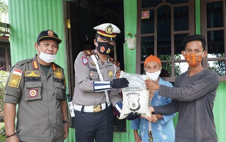 Kasatlantas Polres Katingan bersama anggota komunitas peduli lalu lintas memberikan paket sembako kepada warga Kasongan.