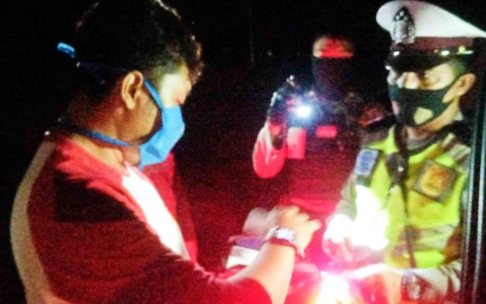 Polisi memeriksa pengendara yang melintas saat razia cipta kondisi di Jalan Trans Kalimantan, Kecamatan Sebangau, Palangka Raya, Kamis malam, 13 Agustus 2020.