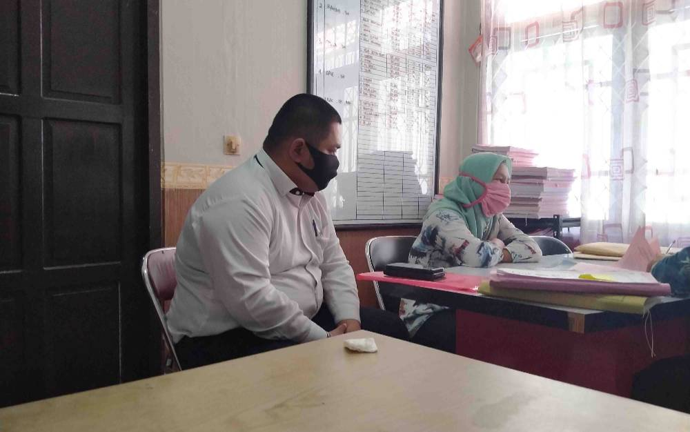 Tersangka pengoplos beras, LK (berjilbab) didampingi penasehat hukumnya.