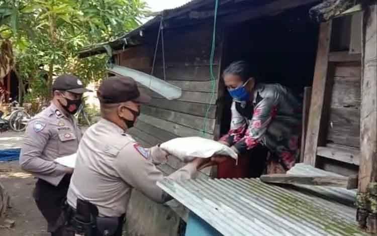 Personel Polsek Kahayan Kuala saat memberikan bantuan beras kepada warga kurang mampu di Bahaur Basantan, Jumat, 14 Agustus 2020.