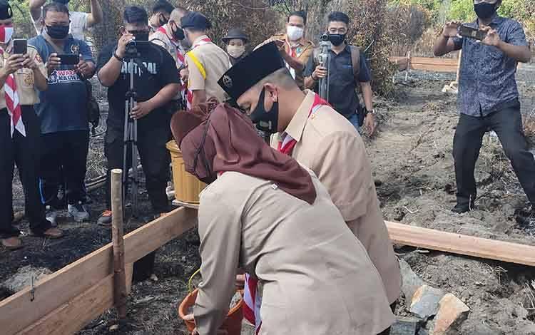 Bupati Sukamara, Windu Subagio didampingi istri saat meletakan batu pertama pembangunan sanggar pramuka.