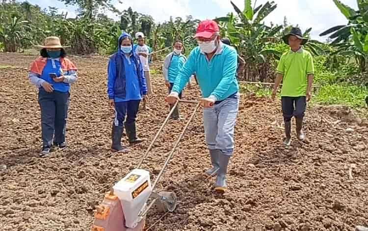 Kepala Dinas Pertanian Kabupaten Barito Timur mencoba alat penanam jagung di Desa Puri Kecamatan Raren Batuah, Jumat 14 Agustus 2020
