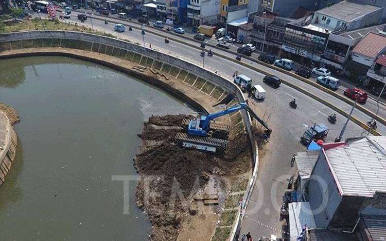 Alat berat mengangkat endapan material lumpur di kali Ciliwung, Jakarta, Kamis, 6 Agustus 2020. Pengerukan ini dilakukan untuk mengurangi pendangkalan sungai dari endapan material lumpur untuk memperlancar arus sungai saat memasuki musim penghujan. TEMPO/Subekti.