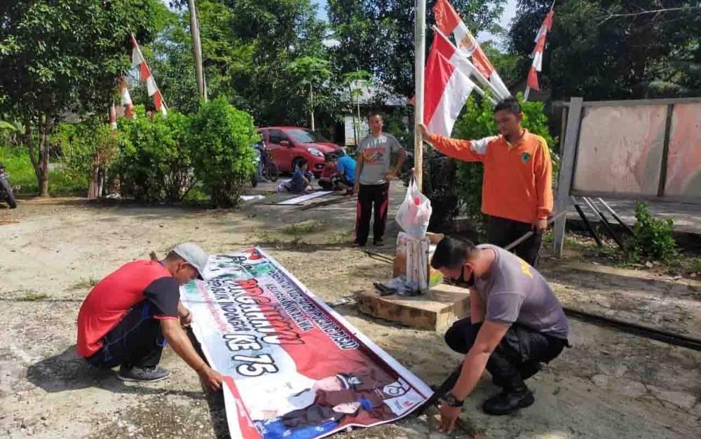 Personel Polsek Kahayan Hilir bersama warga dan mahasiswa memasang spanduk serta bendera untuk menyemarakkan HUT ke 75 Kemerdekaan RI, Sabtu, 15 Agustus 2020.