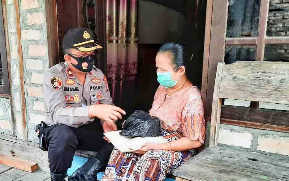 Kapolsek Pahandut, Kompol Edia Sutaata saat menyerahkan bantuan kepada warga kurang mampu.
