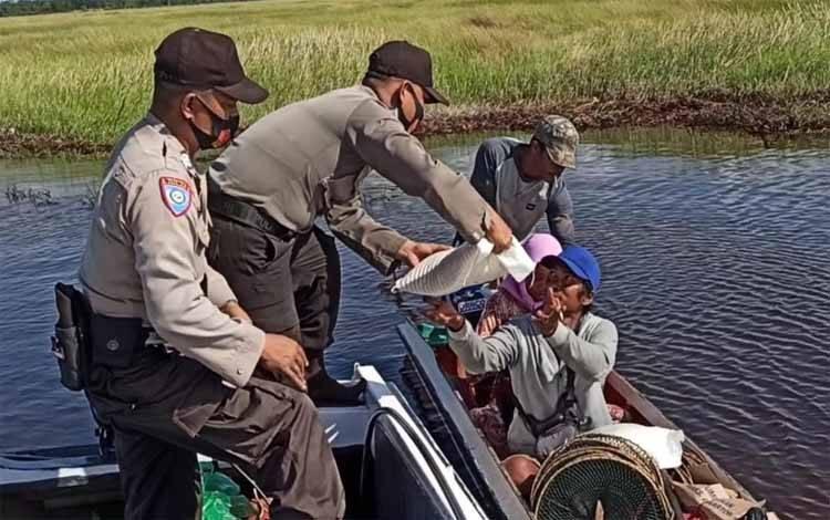 Anggota Polsek Kahayan Kuala memberikan beras kepada nelayan