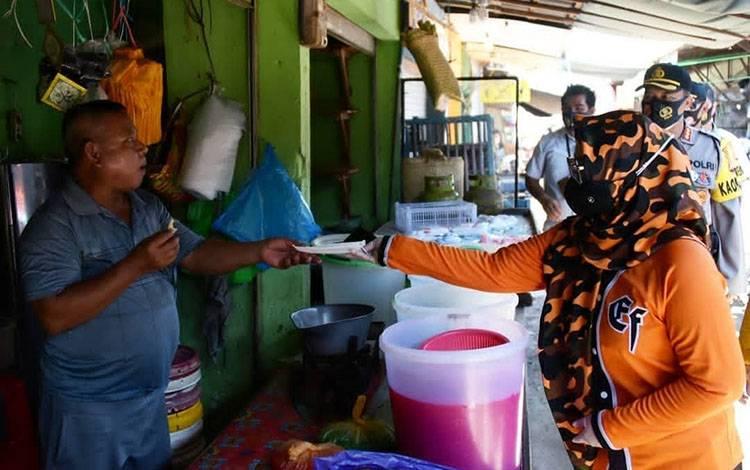 Wakil Wali Kota Palangka Raya Umi Mastikah bersama Satgas Covid-19 membagikan masker di kawasan pasar besar.