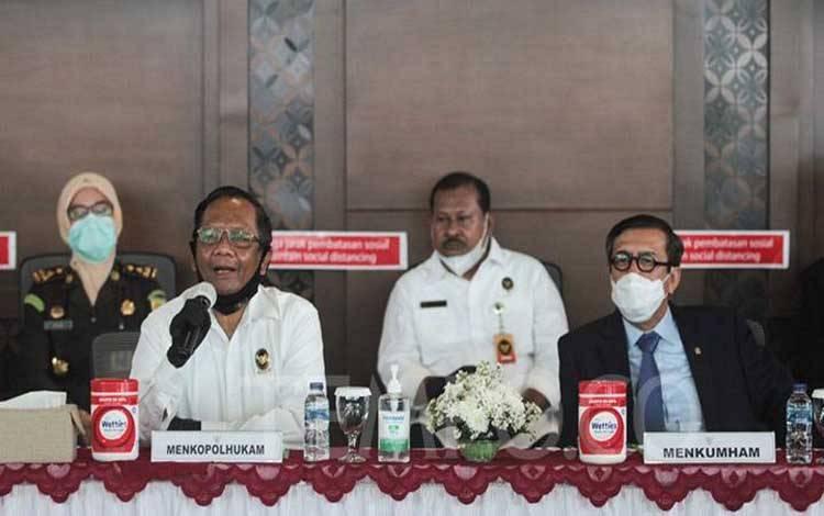Menteri Koordinator Bidang Politik, Hukum dan Keamanan (Menkopolhukam) Mahfud MD (kedua kiri) bersama Menteri Hukum dan HAM Yasonna Laoly (kanan) memberikan keterangan pers terkait penangkapan buronan pembobol kredit BNI sebesar 1,7 Triliun, Marie Pauline Lumowa di Ruang VIP Terminal 3 Bandara Soekarno-Hatta, Tangerang, Banten, 9 Juli 2020. TEMPO / Hilman Fathurrahman W