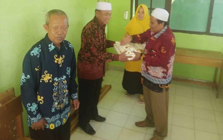 Kepala MIN 3 Kapuas H Saliman saat menyerahkan bingkisan dalam acara perpisahan guru, bertempat di madrasah setempat.