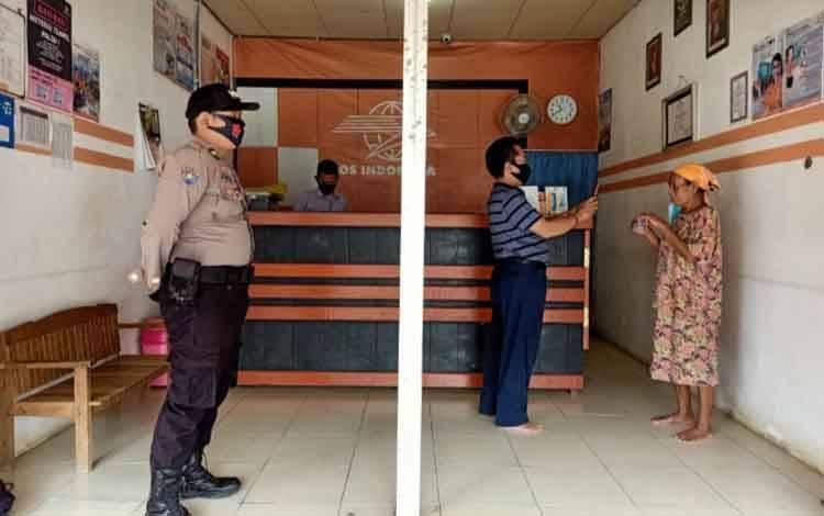 Bhabinkamtibmas Polsek Kahut melakukan pengaman penyaluran BST di Kantor Pos, Senin, 31 Agustus 3020.