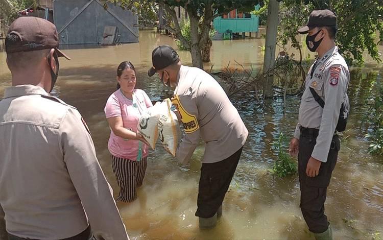 Kabag Ops Polres Katingan AKP M Tommy Palayukan menyerahkan bantuan sembako kepada warga terdampak banjir di Kecamatan Pulau Malan.