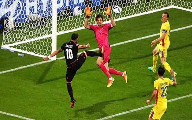 PemainAlbania, Armando Sadiku (liri) mencetak gol pembuka ke gawang Rumania yang dijaga Ciprian Tatarusanu, dalam pertandingan Piala Eropa grup A di Lyon, Prancis, 20 Juni 2016. Julian Finney/Getty Images
