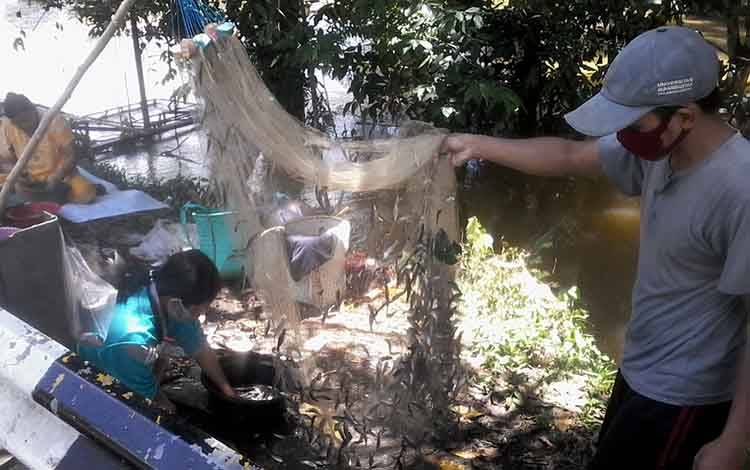 Seorang warga menunjukkan hasil tangkapan ikan saluang di tepi Jalan Tjilik Riwut Km 1,5 Kasongan arah Kereng Pangi
