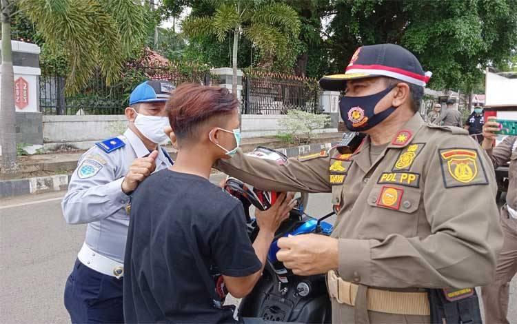 Kepala Satpol PP dan Pemadam Kebakaran Barito Timur, Hudaya Husinsah memakaikan masker kepada pengendara