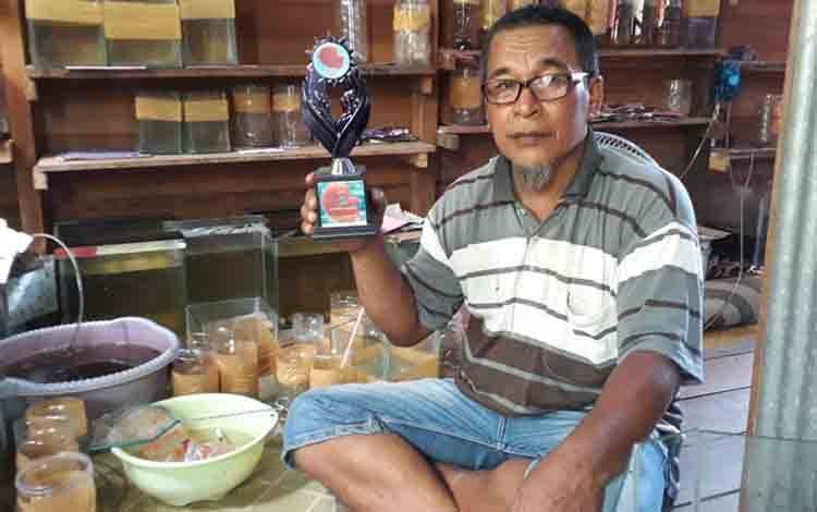 Yusuf (53), saat menunjukan piala juara 1 kontes ikan cupang berlatar belakang jualannya.