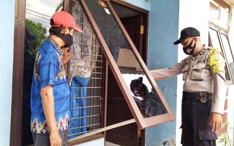 Bhabinkamtibmas Polsek Pahandut Aipda Toha saat menunjukan pintu bekas dicongkel pelaku