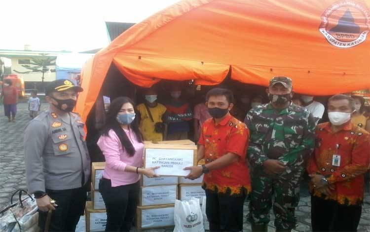 Kapolres Katingan AKBP Andri Siswan Ansyah mendampingi Ketua Cabang Bhayangkari Nadya Andri Siswan menyerahkan bantuan sembako dan pakaian kepada pengungsi banjir