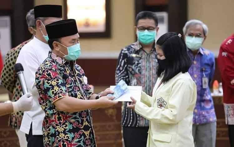 Gubernur Kalteng H Sugianto Sabran saat menyerahkan bantuan dana kuliah secara simbolis untuk mahasiswa, Jumat, 18 September 2020.