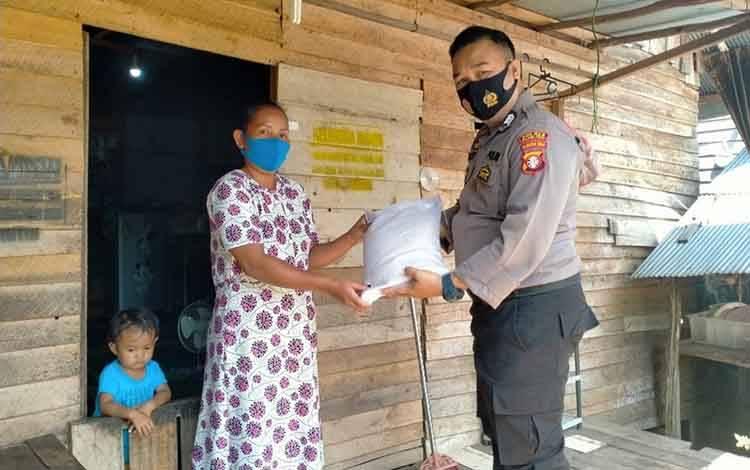 Personel Polsek Kahayan Hilir saat membagikan sembako kepada masyarakat di Desa Mintin, Jumat, 18 September 2020.