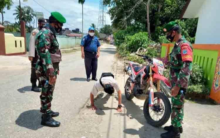 Personel TNI dan Polri di Kecamatan Tewah saat memberikan sanksi kepada warga yang melanggar protokol kesehatan saat beraktivitas di luar rumah