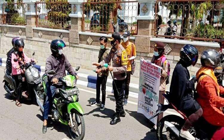 Kapolres Barito Utara AKBP Dodo Hendro Kusuma membagikan masker Samsul Astorijaya di halaman kantor bupati, Minggu 20 September 2020