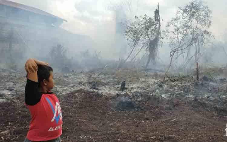 Dua orang anak-anak melihat kebakaran lahan yang terjadi di Jalan Pramuka, Senin, 21 September 2020.