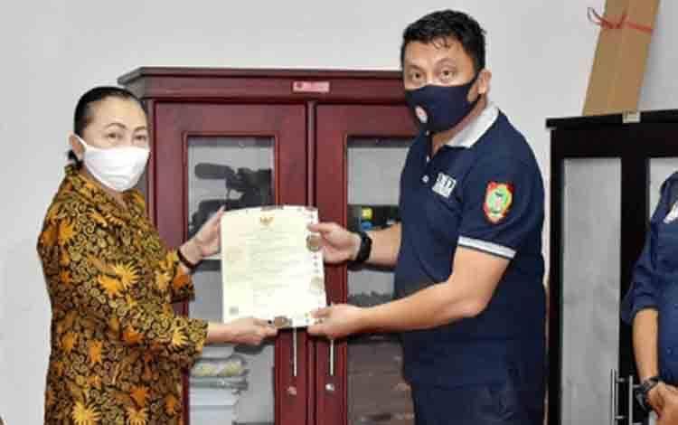 Sekretaris Diskominfo PS Gunung Mas,  Turina Baboe ketika menerima IPP dari Ketua KPID Kalteng Henoch Rents Katopo di Kantor KPID Kalteng.