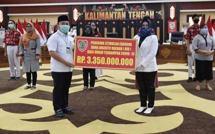 Gubernur Kalteng H Sugianto Sabran menyerahkan bantuan secara simbolis kepada Wakil Walikota Palangka Raya Umi Mastikah.