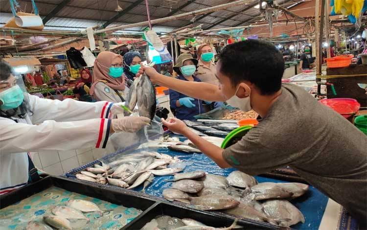 Seorang pedagang memberikan ikan kepada Stasiun Karantina Ikan, Pengendalian Mutu dan Keamanan Hasil Perikanan Palangka Raya untuk dilakukan uji sampel, Rabu 23 September 2020