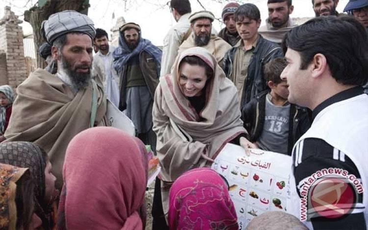 Duta amal UNHCR Angelina Jolie menyumbangkan alat-alat pendidikan kepada kepala sekolah setempat, Gul Rahman, dan murid sekolah perempuan di Desa Qala Gudar, distrik Qarabagh sekitar 28 km di luar Kabul, Afghanistan, Selasa (1/3/2011). Menurut badan tersebut, Jolie akan menyumbang untuk sekolah dasar baru bagi perempuan . (FOTO ANTARA/REUTERS/UNHCR/Jaso)