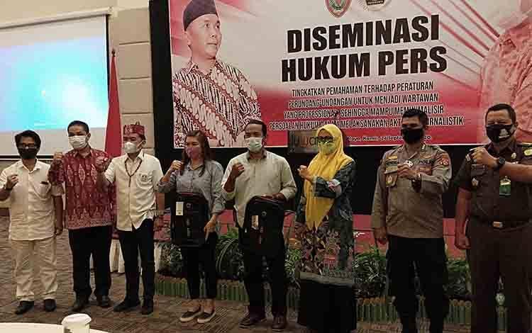 Sejumlah pejabat dan wartawan foto bersama seusai penyerahan cindera mata pada kegiatan Diseminasi Hukum Pers, Kamis, 24 September 2020.