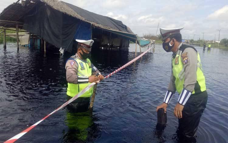 Anggota Satlantas Polres Kobar pasang tali pembatas di jalan yang tergenang banjir