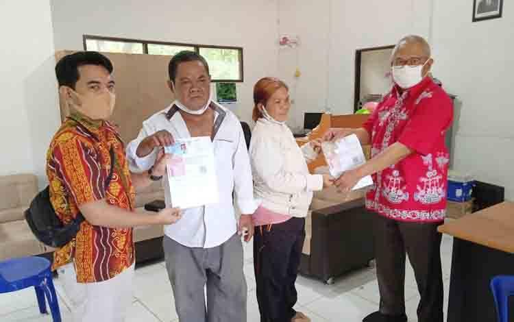 Kepala Dinas Sosial Kabupaten Barito Timur, Riza Rahmadi dan petugas dari Kantor Pos Tamiang Layang saat menyerahkan BST secara simbolis.