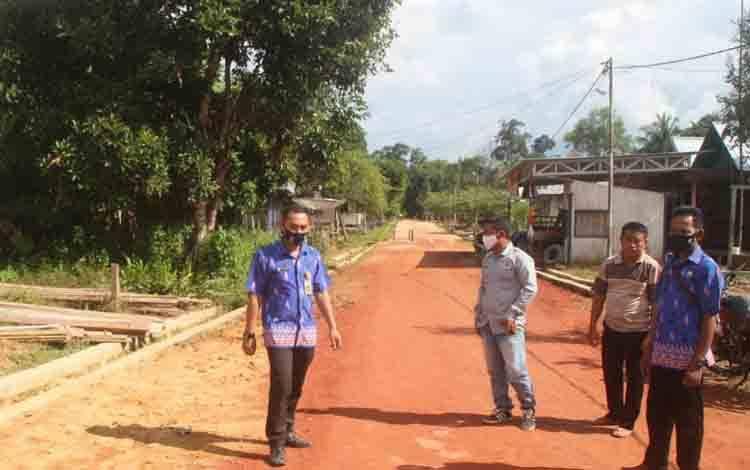 Kades Lubuk Hiju Amos Yanto didampingi Sekdes Salomo, saat menunjukkan lokasi jalan yang akan dicor beton.