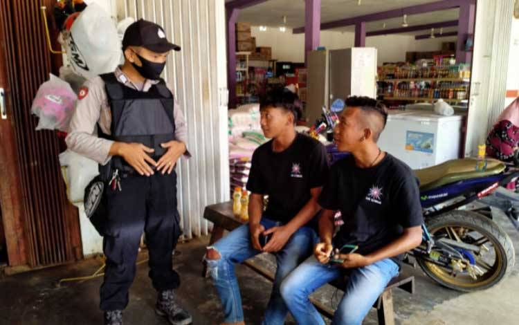 Personel Polsek Manuhing memberikan teguran kepada masyarakat yang melanggar protokol kesehatan saat pelaksanaan operasi yustisi