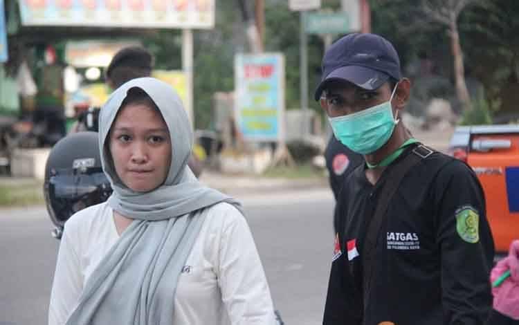 Anggota Satgas Covid-19 Palangka Raya saat memberikan sanksi bagi warga yang tidak pakai masker