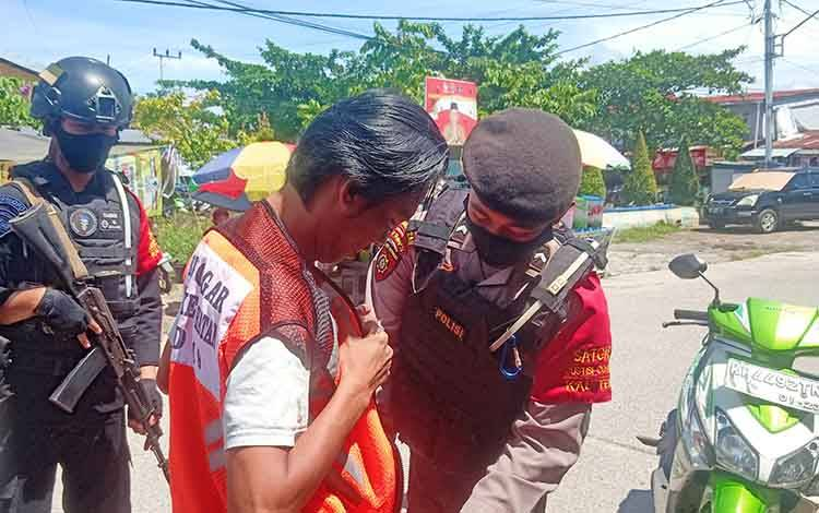 Petugas saat memakaikan baju pelanggar Prokes bagi warga tidak menggunakan masker saat berkendara di kawasan Pasar Kahayan.