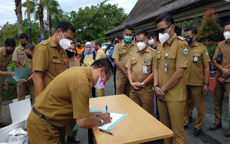 Salah seorang camat saat sedang menandatangani penerimaan bantuan, dengan disaksikan bupati. Sementara, 3 Plt Camat di Kotim diganti Plt Camat yang baru
