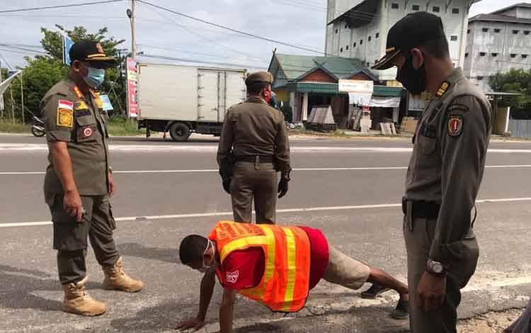 Salah satu warga yang terjaring operasi diberi hukuman push-up oleh tim gabungan dari Satpol PP,  TNI dan Polri.